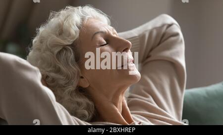 Calm senior woman relax on sofa breathing fresh air - Stock Photo