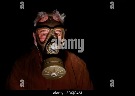 Uncertain times. Fearing the coronavirus, an older man has put on his old gas mask to protect himself. - Stock Photo