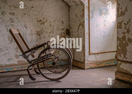Empty wheelchair facing a window in an abandoned asylum - Stock Photo