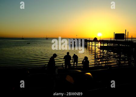 View out across the Solent to the mainland over Totland Pier isle of Wight at sunset yachts kayakers beachgoers in silhouette orange glow of twilight - Stock Photo