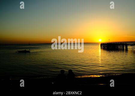 View out across the Solent to the mainland over Totland Pier isle of Wight at sunset with anchored speed boat beachgoers yachts in silhouette - Stock Photo