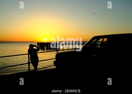 View out across the Solent to the mainland over Totland Pier isle of Wight at sunset with photographers and their vehicle in foreground silhouette - Stock Photo