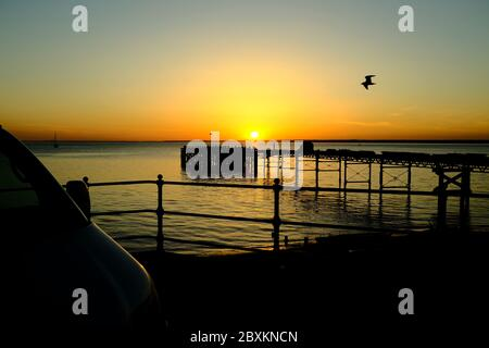 View out across the Solent to the mainland over Totland Pier isle of Wight at sunset yacht seagull orange glow twilight - Stock Photo