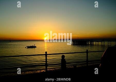 View out across the Solent to the mainland over Totland Pier isle of Wight at sunset with anchored speedboat yacht and kayakers in silhouette - Stock Photo