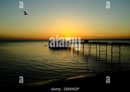 View out across the Solent to the mainland over Totland Pier isle of Wight at sunset yacht seagull kayak orange glow twilight - Stock Photo