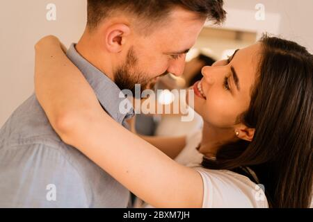 Portrait lovely couple hugging each other, smiling, enjoying time together - Stock Photo