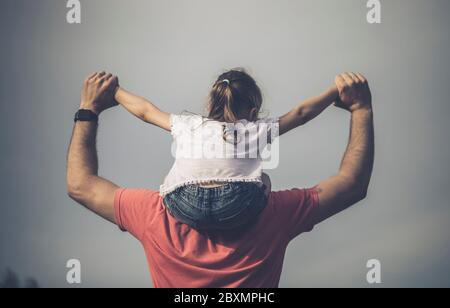 Family values. Father and daughter meet the sunset. He will put the girl on his shoulders and hold her hands. Fathers day concept.
