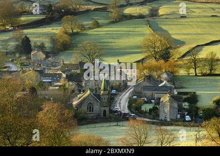Burnsall (scenic Yorkshire Dales village) in valley, attractive cottages, country lane, green hillside fields (sunny winter morning) - England, GB, UK
