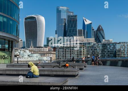 Visitors to the South Bank enjoying a beautiful warm day out by the Thames river with a view of the City of London. England.UK. - Stock Photo