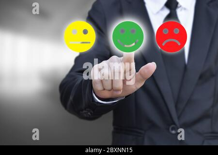 Businessman pressing smiley face icon on virtual screen. Concept of satisfaction evaluation and feedback. - Stock Photo