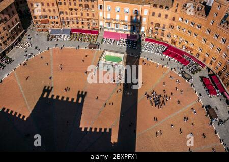 the town hall palace of Siena shot from high to bottom projected its shadows on the famous historical Campo city square