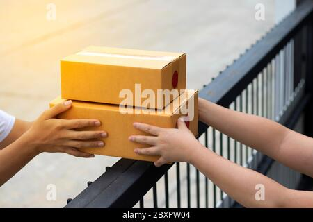 Courier service is delivering the brown box to the recipient. The shipping company delivers the goods to the recipient at the front door.