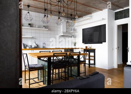 Modern scandinavian an eat-in kitchen interior design with big wooden table and chairs against light wood floor, bright white walls and furnitures - Stock Photo