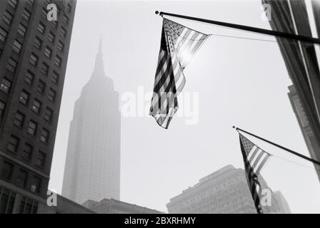 Black and white art photo from New York City with US flags hanging from buildings backlit from sun reflections and Empire State building gray in the d