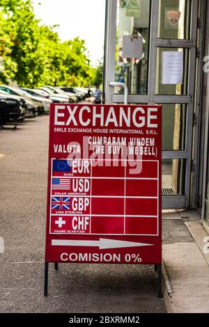 The exchange rate of the main currencies is displayed on a red board at the entrance of a currency exchange office in Bucharest, Romania, 2020 - Stock Photo