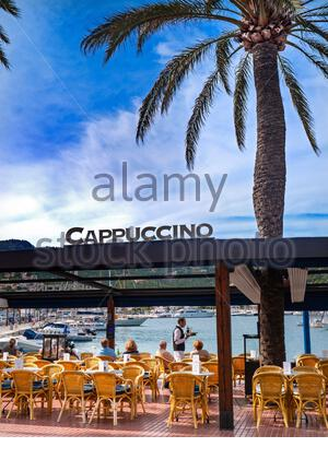 ANDRATX WAITER SERVICE MALLORCA SEAFRONT ALFRESCO BAR CAFE CAPPUCINO PALM TREE  Coastal alfresco luxury waterside Cappuccino Restaurant cafe and bar in Puerto Andratx Mallorca Balearic Islands Spain - Stock Photo