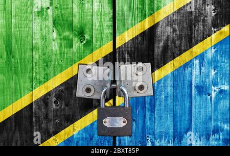 Tanzania flag on door with padlock - Stock Photo
