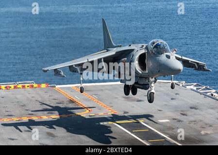 A McDonnell Douglas AV-8B Harrier II fighter jet of the Spanish navy is ready to land at the Juan carlos I aircraft carrier of the Spanish navy. - Stock Photo