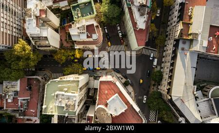 Aerial view of the residential buildings with the main street, autumn trees, colorful cars passing by, different rooftops. - Stock Photo