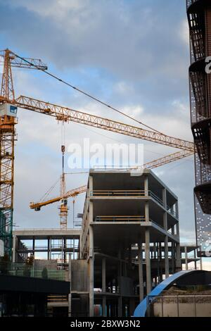 Concrete construction site with two cranes. Blue sky at day time on site. Huge crane rising between two buildings under construction - Stock Photo