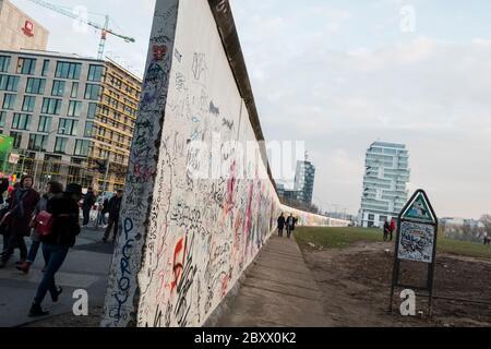 Graffiti on section of original Berlin Wall near River Strass & Muhlenstrasse - Stock Photo