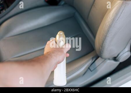 Man's hand holding cleaning spray to clean the car. - Stock Photo