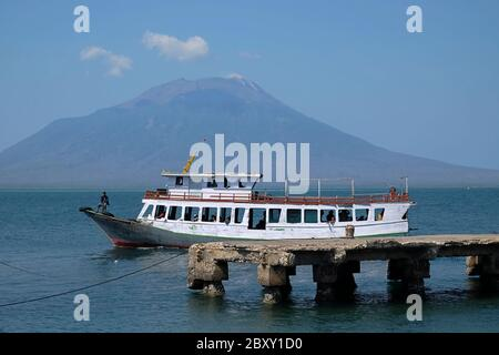 A wooden passenger ship moving on the coastal water of Lewoleba, with Lewotolok volcano can be seen in the background. - Stock Photo