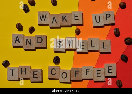 Wake Up And Smell The Coffee, words in 3d wooden alphabet letters with coffee beans isolated on brightly colour background - Stock Photo