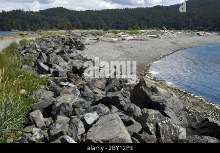 Riprap runs along the ocean side of Whiffin Spit in Sooke, British Columbia, Canada on Vancouver Island. Riprap is rock or other material placed along - Stock Photo