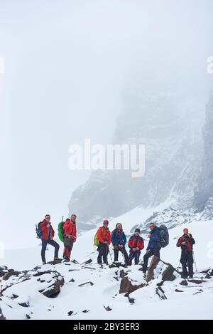 Male tourists with backpacks and trekking sticks taking break during hike in winter mountains. Hikers team standing on rocks covered with snow. Concept of travelling, hiking and tourism. - Stock Photo