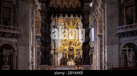 A view towards the altar and papal chair in St Peter's Basilica, Vatican City, between the spiral columns of Bernini's Baldacchino. - Stock Photo