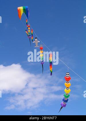 A  collection of multi colored kites against a bright blue sky.