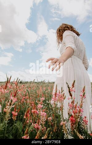 Back view on an angle of young woman in white long dress walking with hand out in a blossoming flower field