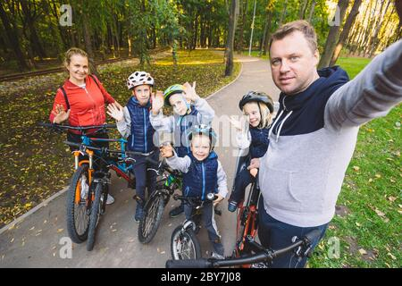 The theme family sports outdoor recreation. large family Caucasian 6 people mom dad and 4 children three brothers and sister ride bicycles in park on - Stock Photo