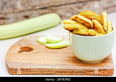 Fried courdette slices in a bowl on wooden background. Home cooking. Healthy eating concept. Selective focus - Stock Photo