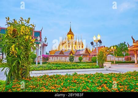 The colorful flowers in evening Mahajetsadabadin park, located in front of Wat Ratchanatdaram Buddhist complex, Bangkok, Thailand - Stock Photo