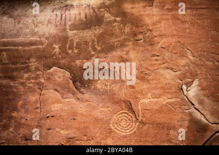 NM00606-00...NEW MEXICO - Rock art along the Petroglyphs Trailshows two styles.. The Puebloan petroglyphs are deeply pecked. The newer Navajo are ligh - Stock Photo