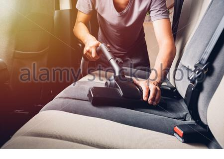 Worker man cleaning dust interior vacuum inside car - Stock Photo