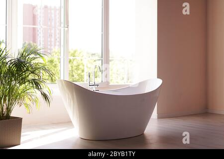 Modern bathroom. White bath with green palm branches. Bright room with sunlight from a large window - Stock Photo