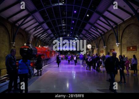 London, UK -  February 2020: Visitors at platform 9 3/4 and Hogwarts Express in Warner Brothers Harry Potter Studio Tour.