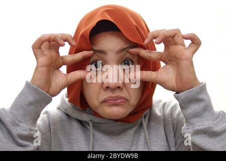 Tired muslim woman open her eyes with finger, trying to keep awake, close up portrait isolated on white - Stock Photo