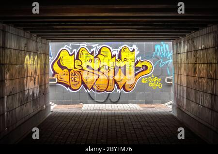 Dark tunnel with grafiti on the wall - Stock Photo