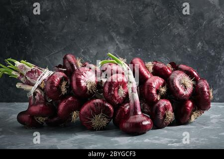 Red onions on a gray background, fresh organic vegetables. Kitchen and cooking concept. Ingredient for salads, soups, dishes.