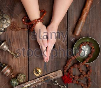 two hands in a prayer pose on a wooden brown table in the middle of vintage Tibetan meditation tools, alternative medicine, top view - Stock Photo
