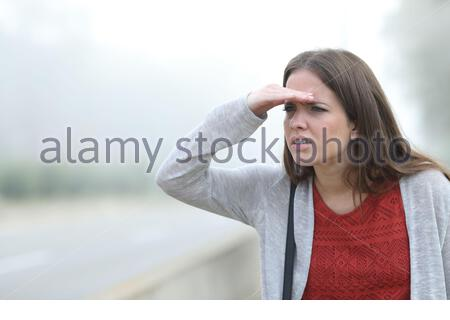 Worried woman trying to watch something a foggy day in a park - Stock Photo