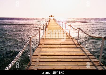 Pier in the sea. Landscape of Wooded bridge in the port between sunrise - Stock Photo