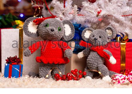 Two homemade plush mice under the Christmas tree with gifts - Stock Photo