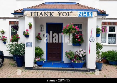 A sign saying Thank You NHS hanging above the porch of a Suburban House with colourful hanging baskets in. South West London. - Stock Photo