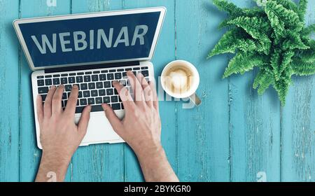 above view of person using laptop computer on wooden table to participate in webinar, online education and e-learning concept - Stock Photo