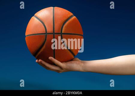 Close up of professional basketball player holding a ball in the hand. Street basketball athlete with a ball and blue sky in the background